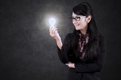 Asian businesswoman looking at a bright bulb Stock Photos