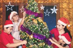 Asian family having fun with Christmas tree Stock Photos