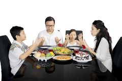 Asian family praying before having meals on studio Stock Images