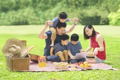 Asian family with a laptop in the park. Picture of Asian family using a laptop while enjoying holiday and picnicking in the park Royalty Free Stock Photo