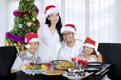 Asian family having Christmas dinner together. Picture of Asian family wearing Santa hat while having Christmas dinner together at home Royalty Free Stock Images