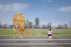 Asian obese woman chased by a fried chicken royalty free stock photo