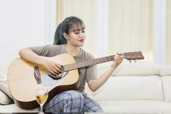 Asian woman learning to play an acoustic guitar. Picture of Asian young woman learning to play an acoustic guitar while sitting in the living room stock photos