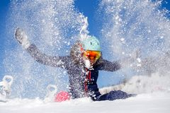 Picture of athlete woman sitting in snowdrift , throws snow Royalty Free Stock Photography