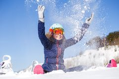 Picture of athlete woman sitting in snowdrift , throws snow Stock Images