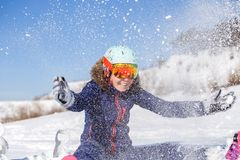 Picture of athlete woman sitting in snowdrift , throws snow Stock Photography