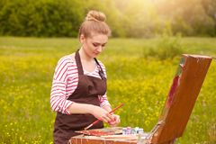 Picture of attractive concentrated young Caucasian female standing with palette of colours, holding tube of oil paint, mixing stock photos