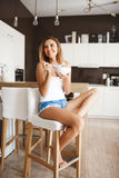 Picture of attractive young girl eating cornflakes with milk at kitchen Stock Photos