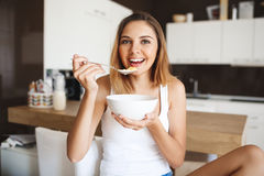 Picture of attractive young girl eating cornflakes with milk at kitchen Royalty Free Stock Photo