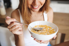 Picture of attractive young girl eating cornflakes with milk at kitchen Royalty Free Stock Images
