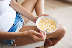 Picture of attractive young girl eating cornflakes with milk at kitchen Stock Photography