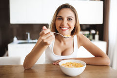 Picture of attractive young girl eating cornflakes with milk at kitchen lookig at camera smiling Stock Photos