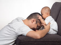 Baby kiss dad. Picture of baby kissing father head on the sofa on white background Royalty Free Stock Images