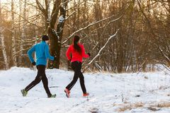Picture from back of sports man and woman on morning run in winter. Picture from back of sports men and women on morning run in winter park Stock Photos