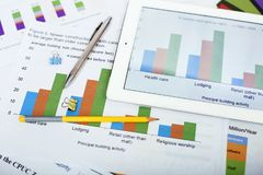 Picture of bar graph on paper and tablet. Portrait of pen and pencil on the paper royalty free stock photos