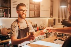 A picture of barman standing behind the bar stand and holding a cup of coffe that he did for the customeer. The barman. Looks happy and smiling while getting a Stock Photo