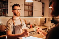 A picture of bearded barmen that wears glasses standing behind the bar stand and holding a cup of coffe that he did for. The customer. The barman looks serious Stock Photos