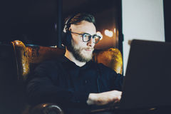 Picture bearded businessman wearing glasses relaxing modern loft office.Man sitting in vintage chair,listening music Stock Photography