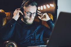 Picture bearded man wearing glasses relaxing modern loft office.Hipster sitting vintage chair,listening music laptop Royalty Free Stock Photography