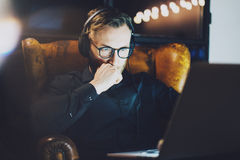 Picture bearded man wearing glasses working modern loft office. Young banker sitting vintage chair,listening music
