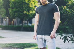 Picture Bearded Muscular Man Wearing Black Blank t-shirt in summer time. Green City Garden.Relaxing time after hard work. Day. Blurred Background.Front view Stock Photography