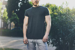 Picture Bearded Muscular Man Wearing Black Empty t-shirt and shorts in summer holiday. Green City Garden Park Background. Front view. Horizontal Mockup Stock Photography