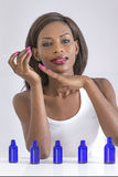 Picture of beautiful african woman smelling perfume on her hand royalty free stock image
