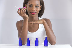 Picture of beautiful african woman smelling perfume on her hand royalty free stock photos
