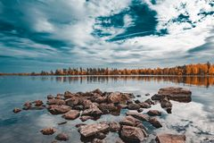 Picture of beautiful autumn lake with yellow and green trees and reflection of blue cloudy sky on the water. Picture of beautiful autumn lake with yellow and stock image