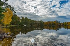 Picture of beautiful autumn lake with yellow and green trees and reflection of blue cloudy sky on the water. Picture of beautiful autumn lake with yellow and royalty free stock image