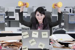 Beautiful businesswoman holding two dumbbells Stock Image