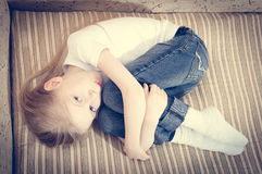 Picture of beautiful child blond girl lying on the sofa hugging knees & looking at camera Stock Photo