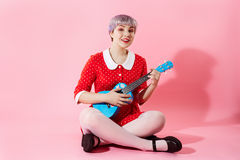 Picture of beautiful dollish girl with short light violet hair wearing red dress playing blue ukulele over pink Royalty Free Stock Images