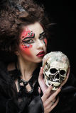 Picture a beautiful fantasy woman with skull. Halloween theme. Royalty Free Stock Photos