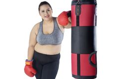 Beautiful fat woman leaning on a bag boxing. Picture of beautiful fat woman smiling at the camera while leaning on a bag boxing, isolated on white background royalty free stock photo