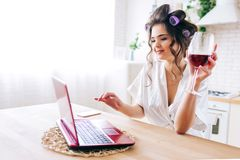 Picture of beautiful housekeeper watching movie on laptop and drink wine in kitchen. Work at home. Careless housewife. Home alone. Curlers in hair stock image