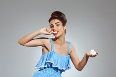 Picture of beautiful pin-up girl eating sweeties at studio Royalty Free Stock Photos