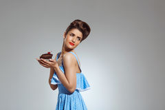 Picture of beautiful pin-up girl holding cake in hands at studio Royalty Free Stock Image