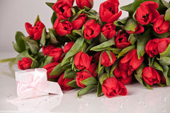 Picture of beautiful tulips with gift box, indoor decorations. Royalty Free Stock Photography