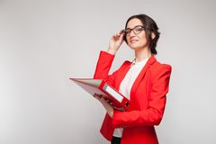 Picture of beautiful woman in red blazer standing with documents in hands Royalty Free Stock Image