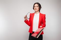 Picture of beautiful woman in red blazer standing with documents in hands Stock Images