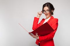 Picture of beautiful woman in red blazer standing with documents in hands Royalty Free Stock Images
