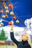 Picture of beautiful woman touching Christmas balls on tree stock photography