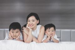 Beautiful woman with her sons on the bed. Picture of beautiful women looking at the camera while lying with her sons on the bed stock photography
