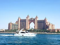 Picture of a beautiful yacht passing in front of the Atlantis the famous 5 stars hotel located on Palm Jumeirah in Dubai. royalty free stock photography