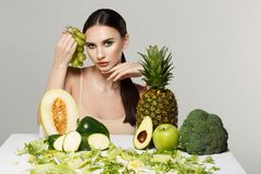 Picture of beautiful young brunette woman with fruits and vegetables on the table stock photography