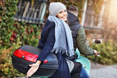 Beautiful young couple smiling while riding scooter in city in autumn royalty free stock photos