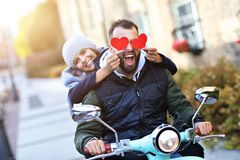 Beautiful young couple holding hearts while riding scooter in city in autumn stock photos