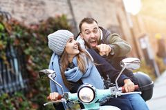 Beautiful young couple smiling while riding scooter in city in autumn royalty free stock image