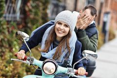 Beautiful young couple smiling while riding scooter in city in autumn royalty free stock photo